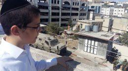 Een Joodse jongen bidt onder legerbegeleiding bij een heilig graf in Hebron. Beeld: Vincent Lengkeek